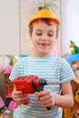 Boy in plastic helmet with toy drill Stock Image