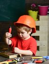 Boy play as builder or repairer, work with tools. Kid boy in orange hard hat or helmet, study room background. Childhood