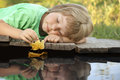 Boy play with autumn leaf ship in water, chidren in park play wi Royalty Free Stock Photo