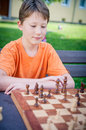 Boy play Chess with Concentration Royalty Free Stock Photos