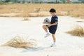 Boy Play Football On The Dry S...
