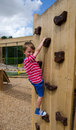 Boy on playground climbing wall Stock Image
