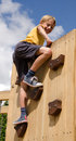 Boy on playground climbing wall reaching the top of Royalty Free Stock Photo