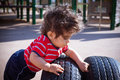 Boy in playground one year old baby playing on a rubber tire outdoor Royalty Free Stock Photo