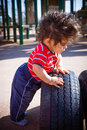 Boy in playground one year old baby playing on a rubber tire outdoor Royalty Free Stock Photography