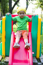 Boy on playground slide Stock Image