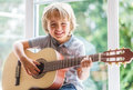 Boy playing acoustic guitar happy smiling learning to play the Royalty Free Stock Photo