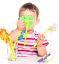 Boy is playing with artificial flowers toys cute little isolated over white Royalty Free Stock Images