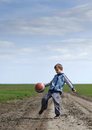 Boy playing with a ball on the mud road Royalty Free Stock Image