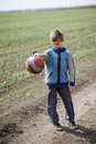 Boy playing with a ball on the mud road Stock Image