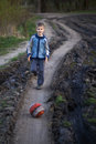 Boy playing with a ball on the mud road after rain Stock Photography