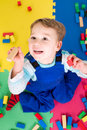 Boy playing with building blocks little on a colorful playmat Stock Photography