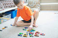 Boy playing with car collection on carpet.Child play home. Transportation, airplane, plane and helicopter toys for children Royalty Free Stock Photo