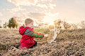 Boy playing with cat by a pond child and long piece of grass to entice the to jump field and background Stock Photo