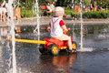 A boy is playing in the city fountain at hot weather Royalty Free Stock Photo