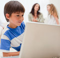Boy playing computer games with his family behind him Stock Images