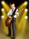 Boy playing on electric guitar on the stage a young white with bright yellow projector behind him Stock Image
