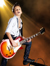 Boy playing on electric guitar on the stage a young white sings and plays with bright lights Stock Photos