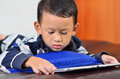 A boy playing a game on computer tablet close up Stock Photography