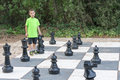 Boy playing giant outdoor chess Royalty Free Stock Photo