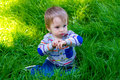 Boy playing in grass a one year old toddler plays the his backyard while waving and looking cute and smiling Royalty Free Stock Photo