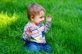 Boy playing in grass a one year old toddler plays the his backyard while waving and looking cute and smiling Royalty Free Stock Photos