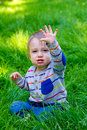 Boy playing in grass a one year old toddler plays the his backyard while waving and looking cute and smiling Stock Photography