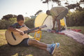 Boy playing guitar while father setting up a tent in background Royalty Free Stock Photo