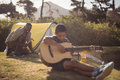 Boy playing guitar while father setting up a tent in park Royalty Free Stock Photo