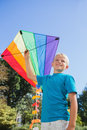 Boy playing with a kite blonde colorful in the park Stock Photo
