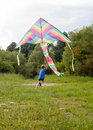 Boy playing with kite happy in field multicolor Stock Photography