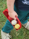 Boy playing minigolf holding a case with balls Stock Image
