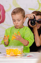 Boy playing and mother taking photo with yellow dough to him Royalty Free Stock Image