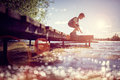 Boy playing on a pier by lake on summer vacation Royalty Free Stock Photo