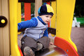 Boy playing on playground little toy hill at Stock Photos