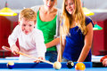 Boy playing pool billiard with family together brother kick off queue and balls on table Stock Image