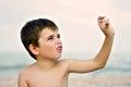 boy playing a seashell on a beach Royalty Free Stock Photo
