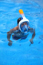 A boy is playing in a swimming pool with Easybreath mask