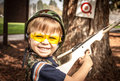 Boy playing with toy crossbow gun young wearing an army costume and safety glasses target shooting in the park Royalty Free Stock Image
