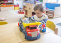 Boy playing with toys in kindergarden at his table Royalty Free Stock Image