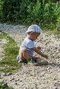 Boy playing two years is in the sand and rocks Royalty Free Stock Images
