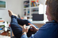 Boy Playing Video Game And Talking On Mobile Phone Royalty Free Stock Photo
