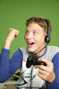 Boy playing video games exited teenage with headphones on his head for wining the game fist in the air holding joystick happiness Royalty Free Stock Images