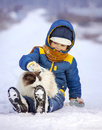 Boy plays with cat outdoors in winter, child petting kitten sitt