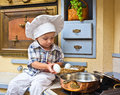 Boy plays the cook little sits on a kitchen table and Royalty Free Stock Photos