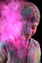 A boy plays holi with colored powder exploding around his face in dark background Royalty Free Stock Photo