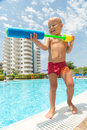 A boy plays with a water pistol near the pool Royalty Free Stock Photos