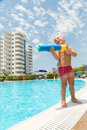 A boy plays with a water pistol near the pool