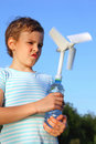 Boy plays with wind-driven generator Stock Photos