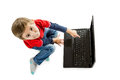 The boy pointing to laptop little in red sweater and jeans sitting on floor and an open top view isolated on white background Royalty Free Stock Photography